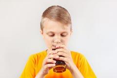 一点切开了喝新鲜的可乐的白肤金发的男孩 免版税库存图片