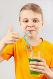 一点切开了喝新鲜的绿色柠檬水的男孩通过秸杆 图库摄影