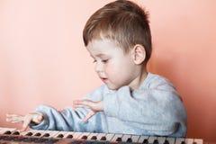 一点切开了弹数字式钢琴的男孩 愉快的童年和音乐 免版税库存图片