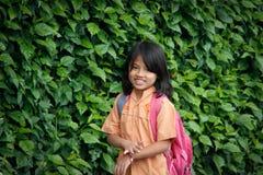 一点印度尼西亚女小学生走与书包反对墙壁的背景有植物的 库存照片