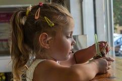 一点吃在咖啡馆的迷人的女婴冰淇淋 库存照片