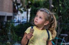 一点吃在街道上的迷人的女婴冰淇淋 库存照片