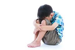 一点哀伤的男孩barefeet坐地板 隔绝在白色后面 免版税库存图片