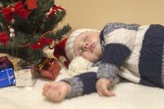 一点圣诞老人的帽子的婴孩睡觉在圣诞树下的 免版税库存图片