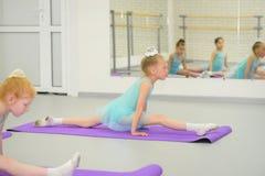 一点在伸展运动期间的芭蕾舞女演员在芭蕾学校课程 库存照片
