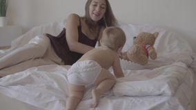 一点在家使用在床上的婴孩 坐在婴儿附近的逗人喜爱的母亲 climbling在床上的可爱的孩子 r 股票视频