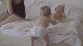一点在家使用在床上的婴孩 坐在婴儿附近的逗人喜爱的母亲 climbling在床上的可爱的孩子 r 影视素材