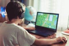 一点在家使用在膝上型计算机的依赖游戏玩家孩子 免版税库存照片