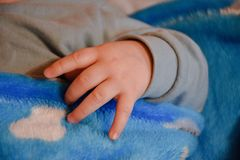 一点在蓝色毯子的婴孩手 免版税库存图片