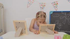 一点坐在桌上的逗人喜爱的女孩在看在框架的儿童房间照片 影视素材