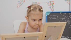 一点坐在桌上的逗人喜爱的女孩在看在框架的儿童房间照片 股票视频