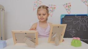 一点坐在桌上的逗人喜爱的女孩在看在框架的儿童房间照片 股票录像