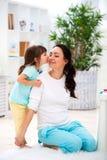 一点女儿拥抱并且亲吻妈妈 愉快的家庭和爱 日母亲s 免版税库存照片
