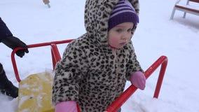 一点女婴摇摆在多雪的冬时的操场 4K 股票视频
