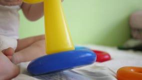 一点婴孩在幼儿园收集金字塔坐床 学龄前年龄的孩子的发展 特写镜头 股票视频