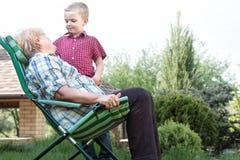 一点孙子拥抱他心爱的祖母 一个家庭周末 参观的祖母 图库摄影