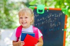 一点学校白肤金发的女孩在有背包的学校教室和 图库摄影