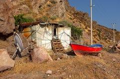 一点小屋和一条小船在小山前面 免版税库存图片