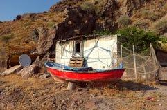 一点小屋和一条小船在小山前面 库存图片