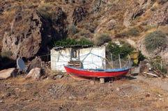 一点小屋和一条小船在小山前面 免版税库存照片