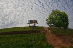 一点小屋和绿色树在小山 库存照片