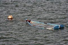 一点小船被放弃海上在卡斯卡伊斯,葡萄牙 库存图片