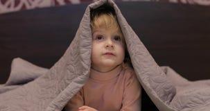 一点快乐的女孩掩藏在毯子和看着电视下 孩子睡眠的概念 股票录像