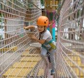 一点愉快和微笑的攀岩运动员栓在绳索的一个结 人为上升做准备 孩子学会栓结 免版税库存照片