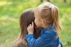一点愉快的女孩在公园拥抱她的妈妈并且告诉她某事在耳朵 免版税库存照片