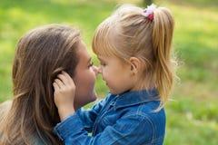一点愉快的女孩在公园拥抱她的妈妈并且告诉她某事在耳朵 免版税图库摄影