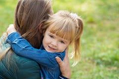 一点愉快的女孩在公园拥抱她的妈妈并且告诉她某事在耳朵 免版税库存图片