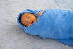 一点新生儿包裹与蓝色毛巾,并且婴孩在灰色地毯睡觉 免版税库存图片