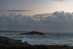 一点有多云天空和波浪的海岛 免版税库存照片