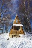 一点木房子在山的一个多雪的冬天森林里在一个冷淡的晴天 旅游胜地, Lago-Naki, Adygeya共和国 免版税库存图片