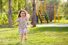 一点步行的愉快的女孩在日落的一个夏天晚上在公园 ?? 免版税库存图片