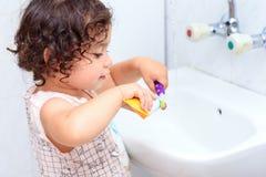 一点清洗她的牙的可爱宝贝女孩与牙刷在卫生间里 库存图片