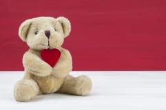 一点熊举行红色心脏 华伦泰概念 库存图片