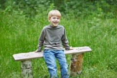 一点牛仔裤的白肤金发的微笑的男孩坐公园长椅 免版税图库摄影