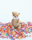 一点玩具熊坐一个五颜六色的糖果店顶部 软的焦点,轻的口气,特写镜头 库存图片