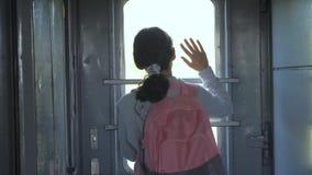 一点生活方式十几岁的女孩是旅行乘火车的背包徒步旅行者 旅行运输铁路概念 旅游学校 股票录像