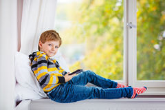 一点男生阅读书或ebook由窗口 免版税库存图片