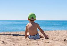 一点男婴坐的使用与沙子 免版税库存图片
