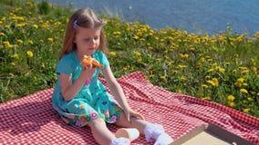 一点白肤金发的女孩在温暖的天吃在海滨的比萨 股票录像