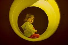 一点白肤金发的女孩戏剧和在玩具管掩藏 免版税库存照片