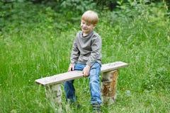 一点白肤金发的微笑的男孩坐公园长椅 库存图片