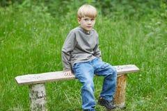 一点白肤金发的微笑的男孩坐公园长椅 库存照片