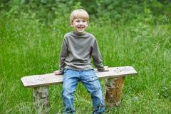 一点白肤金发的微笑的男孩坐公园长椅 免版税库存照片