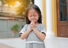 一点祈祷在庭院里的亚洲女孩姿态在早晨 小孩祈祷女孩的手,手在祷告概念折叠了为 免版税库存图片