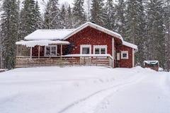 一点红色房子在有雪的森林里 免版税库存图片