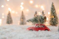 一点红色汽车玩具运载的圣诞树 免版税库存照片